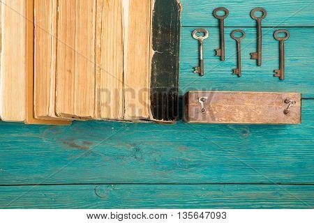 Old Keys And Stack Of Antique Books On Blue Wooden Desk