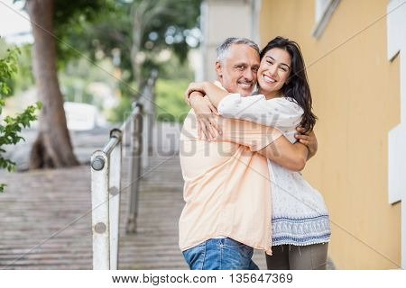 Portrait of happy couple embracing in city
