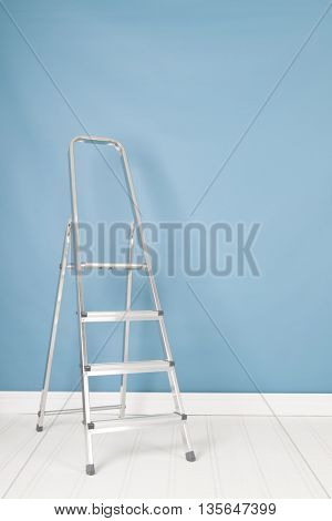 Metal stepladder in blue interior