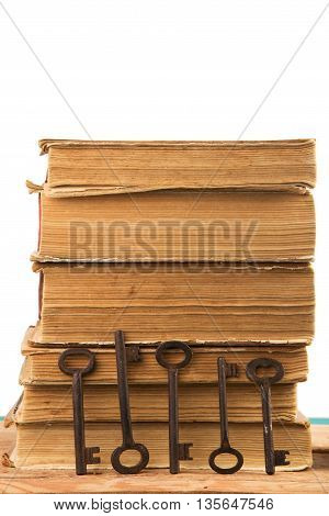 Old Keys And Stack Of Antique Books Isolated On White Background