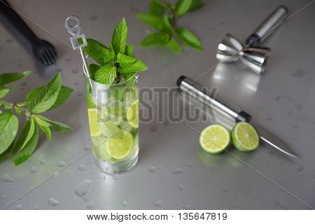 portrait of fresh mojito glass with barman tools