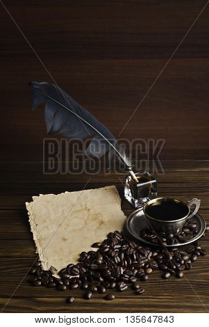 A cup of coffee and old paper with ink and pen on the wooden background