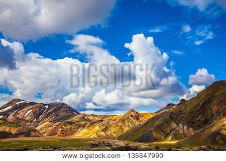 Multi-colored mountains from mineral rhyolite are lit with the July sun. Travel to Iceland in the summer. National park Landmannalaugar