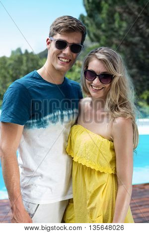 Happy couple in sunglasses standing near the pool on a sunny day