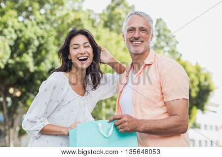 Portrait of happy couple with shopping bags standing outdoors