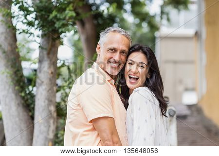 Portrait of cheerful couple standing in city