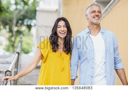 Front view of cheerful couple strolling outdoors