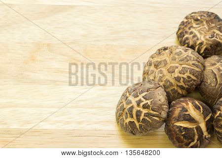 Dried shiitake mushrooms on wooden background with copyspace