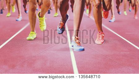 Close up of sportsman legs running against race track