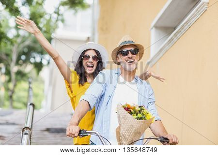 Happy man cycling with excited woman in city