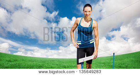 Portrait of sportswoman posing next to hurdle against green field under blue sky