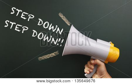 megaphone in front chalkboard with text step down