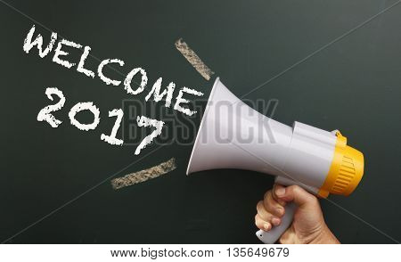 megaphone in front chalkboard with text welcome 2017