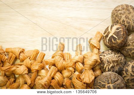 Dried shiitake mushrooms and bean curd on wooden background with copy space ; Frame for food preservation background