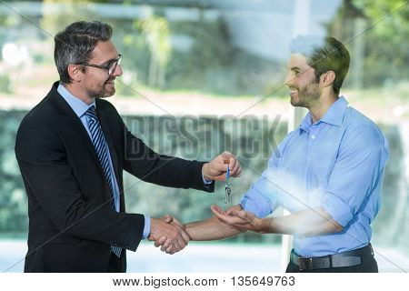 Estate agent giving resort key to man at resort