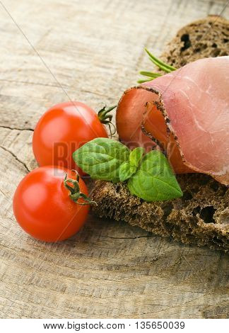 bread with sliced pork ham and tomato on a wooden background