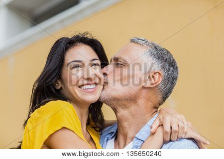 Close-up of man kissing happy woman against wall