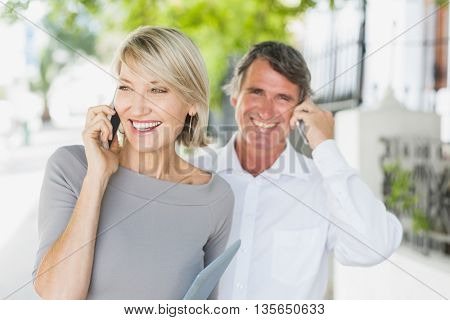 Happy couple talking on phone while standing in city