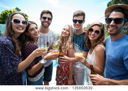 Group of friends holding a glass of cocktail on a sunny day