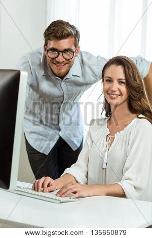 Portrait of male and female collegues using computer at desk in office