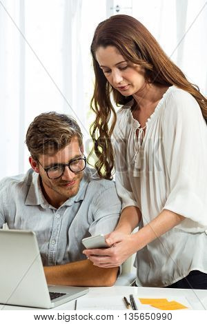 Man and woman using mobile phone at desk in office