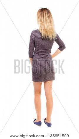 back view of standing young beautiful  woman.  girl  watching. Rear view people collection.   Isolated over white background. The girl in the purple dress standing with hands left.