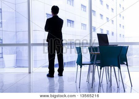 Businessman standing in the office and laptop on the table