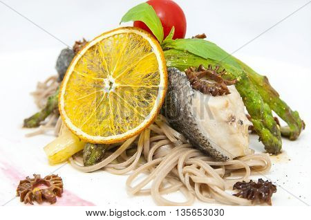 baked fish with spaghetti and mushrooms and vegetables