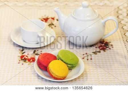 French Colorful Macarons On A Plate, Cup And Teapot