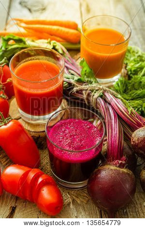 Selection of vegetable juices in glasses and ingredients, copy space, toned