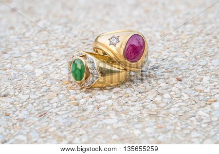 Closeup old green jade and pink pebble rings on blurred stone floor