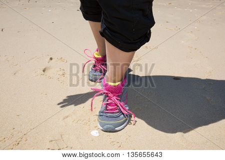 Sportswoman runner getting ready running shoes on the sand