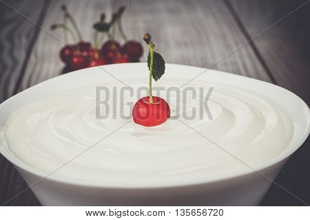 white bowl full of sour cream with cherry on top