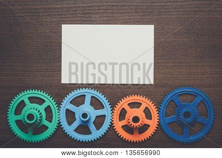 colorful gears and blank notepad on the brown wooden background