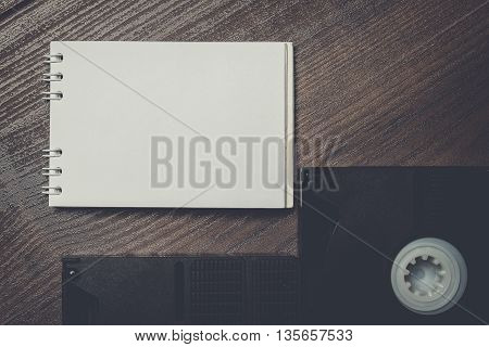 old retro video tapes and notebook on wooden background