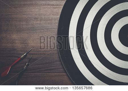 target and two darts on the wooden background