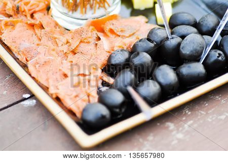 grilled salmon and black olive dish on the table