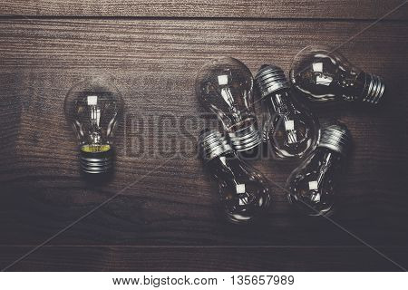bulbs out of the crowd concept on wooden background