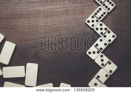 domino pieces on the dark brown wooden table background
