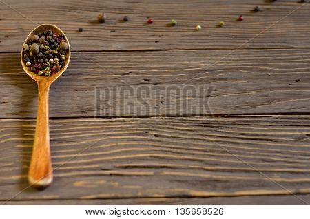 Wooden spoon with colored pepper lies on a rustic wooden table