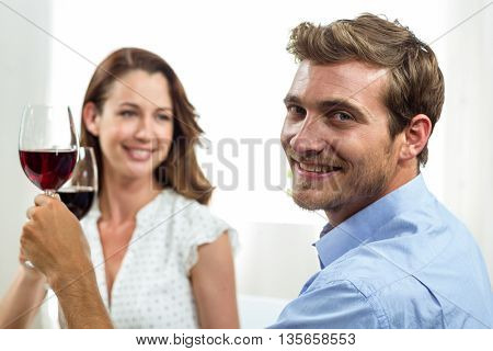 Smiling couple toasting wineglasses at home