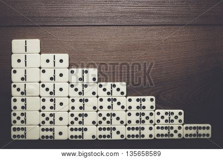 full set of domino pieces over wooden table background
