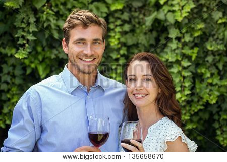 Portrait of happy couple holding wineglasses at front yard