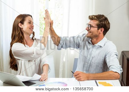 Male and female colleagues giving high five at desk in office