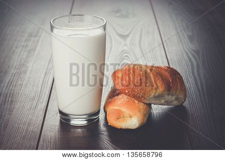 glass of milk and fresh buns on the table