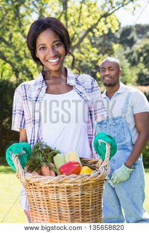 Young woman holding a basket of freshly harvested vegetables in garden
