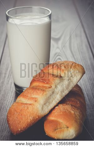 glass of milk and fresh buns on the wooden table