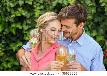 Happy couple embracing while toasting wineglasses at front yard
