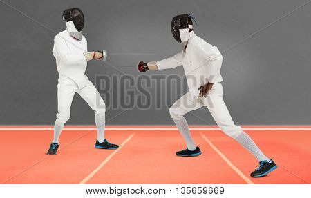 Man wearing fencing suit practicing with sword against digitally generated image of playing field