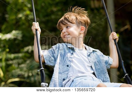Young boy having fun swinging. Smiling child playing on a swing at park. Portrait of happy little boy swinging on swing on a bright sunny day.